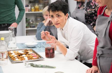 Warsztaty kulinarne z Alessia di Donato w Menora Info przy pl. Grzybowskim. Na zdjęciu: Alessia di Donato w białym kitlu pochyla się nad stołem i tłumaczy coś uczestnikom i uczestniczkom warsztatów