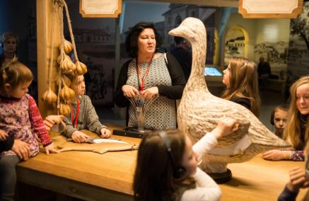 Chanuka w Muzeum POLIN - spacer z przewodnikiem po wystawie dla rodzin z dziećmi - Opis zdjęcia: grupa dzieci stoi wokół drewnianej lady straganu na wystawie muzeum. Słuchają przewodniczki. Na straganie wiszą wieńce czosnku i stoi gęś - wykonane z drewna. Panuje półmrok.