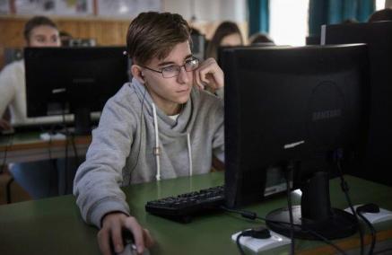 Zajęcia na platformie IWitness, Na zdjęciu: Chłopiec siedzi w ławce przed monitorem komputera