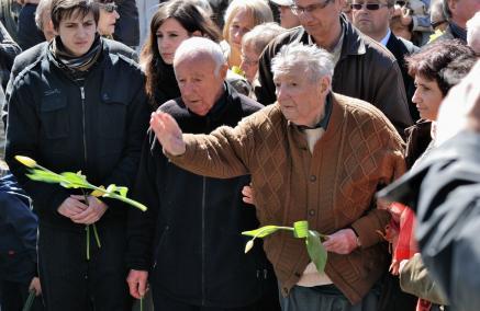 Marek Edelman rzuca kwiaty pod pomnikiem Bohaterów Getta w Warszawie