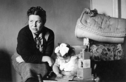 Warszawa Ireny Sendlerowej - spacer z przewodnikiem dla grup szkolnych, Na zdjęciu: Młoda Irena Sendlerowa siedzi na taborecie, obok niej mała dziewczynka w białej sukience siedzi pochylona nad książeczką. Zdjęcie czarno-białe.