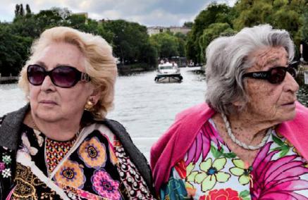 Oma & Bella - film, TISZ Festiwal Żydowskiego Jedzenia - kadr z filmu, przedstawia dwie starsze kobiety, które siedzą obok siebie z głowami odwróconymi od siebie. Każda ma ciemne okulary, narzucony na ramiona sweter oraz barwne bluzki. W tle widok rzeki i miasta położonego na jej brzegach.