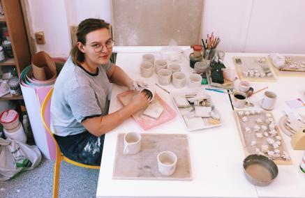 Warsztaty ze zdobienia ceramiki z Trzask - TISZ Festiwal Żydowskiego Jedzenia w Muzeum POLIN. Na zdjęciu kobieta w okularach z włosami spiętymi z tyłu głowy. Widać ją w ujęciu z góry. Siedzi przy stole warsztatowym, przed nią rozłożone przedmioty z ceramiki. Trzyma w ręku kubek.