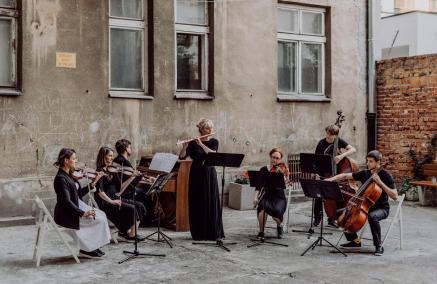 Wajnberg w Warszawie – koncert Hashtag Strings, Ani Karpowicz i Marka Brachy. Na zdjęciu: zespół muzyków grających na instrumentach smyczkowych oraz flecistka i pianista siedzą na podwórku warszawskiej kamienicy i grają koncert