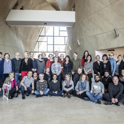 Ambasadorzy Muzeum POLIN. Na zdjęciu grupa mężczyzn i kobiet. Stoją w kilku rzędach - jeden za drugim - w przestronnym holu. Za nimi duże okno od podłogi do sufitu (hol główny Muzeum POLIN).