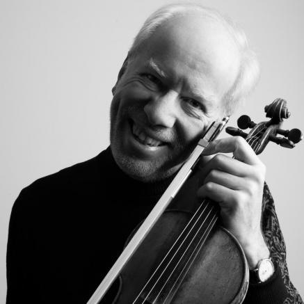 Gidon Kremer - na zdjęciu widzimy Kremera uśmiechniętego, ze skrzypcami przy policzku. Zdjęcie czarno-białe.