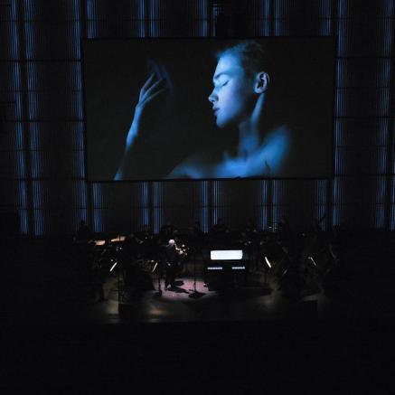 Wajnberg@100. Na zdjęciu kadr z koncertu - scena wraz z widownią kompletnie zaciemniona, nikłe światło skierowane jest na solistę. Na ekranie nad sceną wyświetlone zdjęcie twarzy młodej śpiącej kobiety. Twarz oświetlona niebieskim światłem.