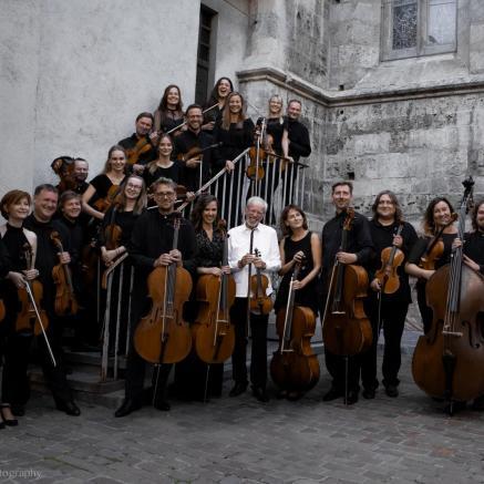 Na zdjęciu Kremerata Baltica z Gidonem Kremerem na czele (w białej koszuli w środku orkiestry). Zespół stoi na dziedzińcu, przed schodami do budynku.