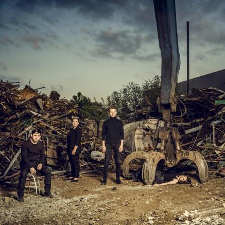 Festiwal Kwadrofonik: Urlicht. Na zdjęciu: w mrocznym, industrialnym otoczeniu siedzą i stoją członkowie zespołu