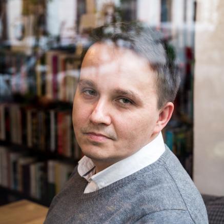 Nominowani do Nagrody POLIN 2019: Mirosław Tryczyk. Na zdjęciu Mirosław Tryczyk siedzi przy drewnianym stoliku patrzy przez ramię. W tle regał z książkami.