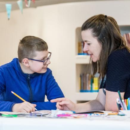 W sali edukacyjnej, gdzie stoją regały z książkami, przy stole siedzi chłopiec w niebieskiej bluzie i kobieta w czarnej koszulce. Chłopiec trzyma w ręku ołówek i słucha kobiety - Muzeum dostępne, warsztaty edukacyjne dla osób z niepełnosprawnościami w Muzeum POLIN