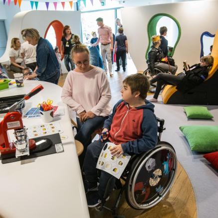 Rosz ha-Szana - warsztaty dla rodzin z dziećmi - dla osób z niepełnosprawnościami w Muzeum POLIN. Na zdjęciu grupa dzieci z opiekunami zajęta jest tworzeniem przy długim białym stole warsztatowym. Stół znajduje sie w kolorowej, przyjaznej przestrzeni miejsca edukacji rodzinnej