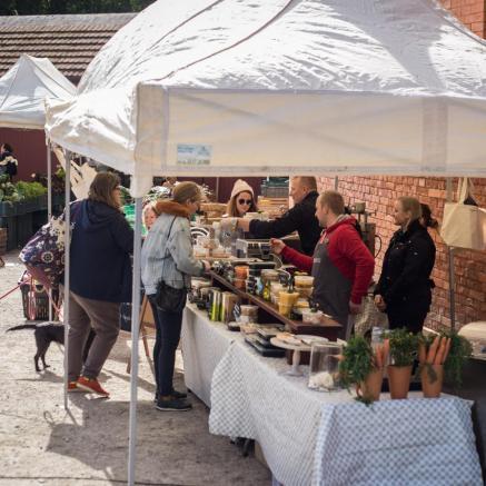 Targ w Fortecy Kręglickich w ramach TISZ Festiwalu Muzeum POLIN, Na zdjęciu: w otwartej przestrzeni, pod ścianami z czerwonych cegieł, rozstawione są stołychronione parasolami. Na stołach porozkładane produkty żywnościowe i warzywa oraz owoce. Wokół straganów ludzie - sprzedawcy i kupujący