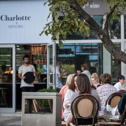 TISZ Festiwal: śniadanie po warszawsku. Na zdjęciu scena przed restauracją Charlotte Menora. Obok białej tabliczki z logo restauracji widać stoliki, przy których, przy śniadaniu, siedzą kobiety i mężczyźni. W tle, w drzwiach do restauracji, widać kelnera w białym podkoszulku. Trzyma czarną okrągłą tacę.