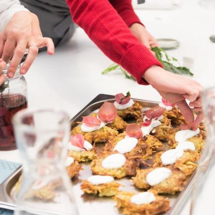 Warsztaty kuchni wegańskiej - TISZ Festiwal Żydowskiego Jedzenia: DOM. Na zdjęciu: przez szyjki karafek z białego szkła widać blachę, na której układane są placki ziemniaczane. Placki przybrane są kleksem śmietany i marynowaną czerwoną cebulą. Blacha stoi na białym stole, w górnej części zdjęcia wydać dwie pary rąk osób, które przygotowują potrawę.