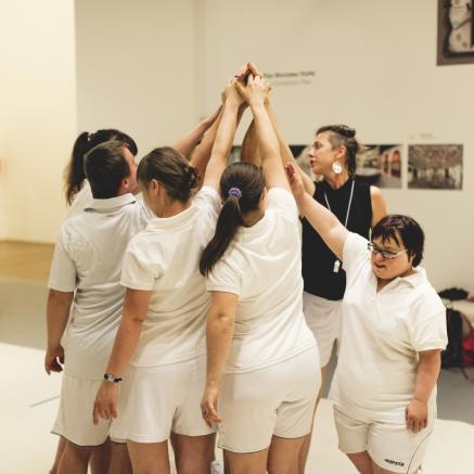 Teatrr 21, w spektaklu Tisza Be-Aw w Muzeum POLIN, Na zdjęciu: grupa aktorów Teatru 21, ubrana w białe spodenki i białe koszulki, wykonuje fragment przedstawienia