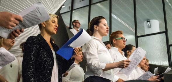 Chór POLIN - Czytanie wystawy Gdynia - Tel Awiw w Muzeum POLIN - na zdjęciu grupa dorosłych osób, ubranych galowo (białe koszule, czarne żakiety i garnitury. Śpiewają. Stoją pod krętymi schodami pomalowanymi na biało.