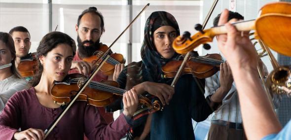 Crescendo #makemusicnotwar, reż. Dror Zahavi, prod. Alice Brauner, Niemcy 2019, 102 min, dramat, Na zdjęciu: grupa kobiet i mężczyzn gra na skrzypcach