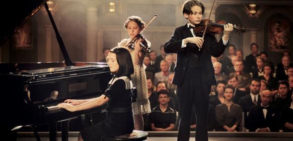 Cudowne dzieci (Wunderkind) - pokaz filmu w ramach WJFF, Na zdjęciu: kadr z filmu, przedstawia troje dzieci, które stoją na scenie i grają: dziewczynka na pianinie, chłopiec i druga dziewczynka na skrzypcach