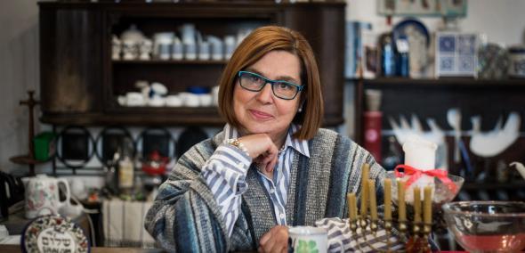 Nominowani do Nagrody POLIN 2019: Krystyna Szter. Na zdjęciu Krystyna Szter siedzi za stołem z brodą podparta na dłoni. Na stole przedmioty związane z kulturą żydowską, np. menora. W tle stary kredens.