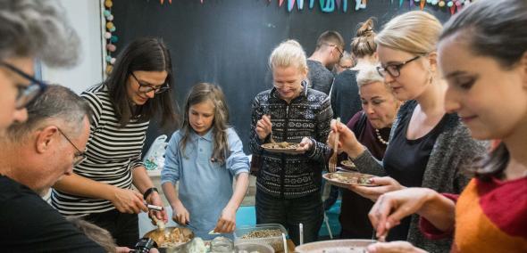 Międzypokoleniowe warsztaty kulinarne w JCC w ramach TISZ Festiwalu Żydowskiego Jedzenia - Muzeum POLIN, na zdjęciu widać młodych i dorosłych stojących wokół kuchennego stołu i zajętych przygotowywaniem potraw. W tle czarna tablica z kolorowymi chorągiewkami