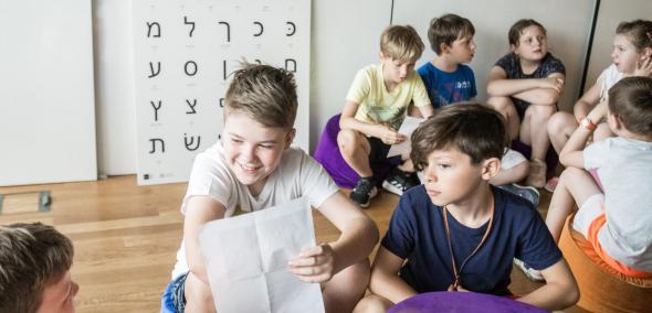 Grupa dzieci w sali, rozmawiają ze sobą. Na pierwszym planie dwóch chłopców - ten po lewej trzyma kartkę i się uśmiecha, drugi po prawej patrzy zasłuchany. Za dziećmi biała plansza z czarnymi hebrajskimi literami. Warsztaty dla szkół podstawowych, klasy 4-6 w Muzeum POLIN