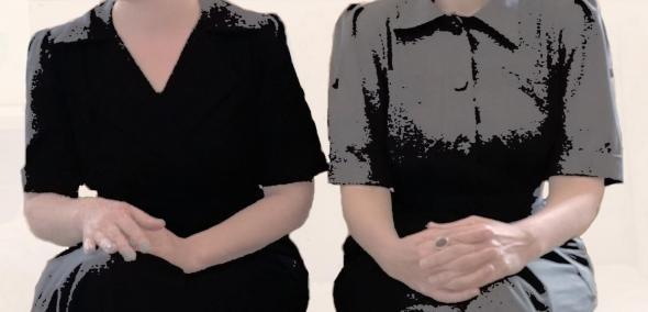 Dwie siedzące kobiety ubrane w czarne sukienki.