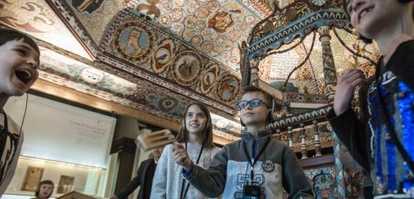 Rodzinne spacery z żydowskimi tradycjami w Muzeum POLIN - grupa dzieci znajduje się na wystawie, pod dachem synagogi (rekonstrukcja). Dach zdobiony jest bogato ornamentami charakterystycznymi dla kultury żydowskiej, w kolorach białym, niebieskim, czerwonym, brązowym. Są tu ornamenty roślinne i przedstawienia zwierząt, reprezentujące zodiak. Jedno z dzieci kręci młynkiem, inne się śmieją.