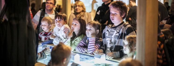 Wokół podświetlonej witryny, w ciemnym pomieszczeniu, stoją dzieci i dorośli, pochylają się nad witryną