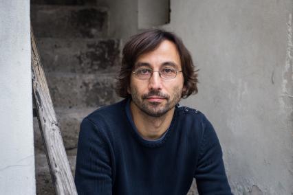 Nominowani do Nagrody POLIN 2019: Adam Musiał. Na zdjęciu Adam Musiał, siedzi na schodach z drewnianą poręczą