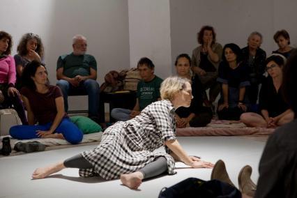 In between - performans Adiny Bar-On w Muzeum POLIN, Na zdjęciu: grupa kobiet i mężczyzn siedzi na podłodze pod ścianami pomieszczenia, na środku podłogi kobieta (Adina Bar-On) w trakcie performansu.