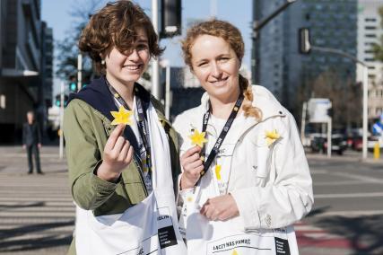 Dwie wolontariuszki akcji Żonkile stoją przy przejściu dla pieszych - przymają w dłoniach papierowe żonkile, które są symbolami akcji