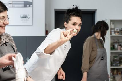 Warsztaty z Malką Kafką. Na zdjęciu Malka Kafka w białym kitlu szefa kuchni, trzyma w palcach kulkę z przekąską zrobioną w czasie warsztatów