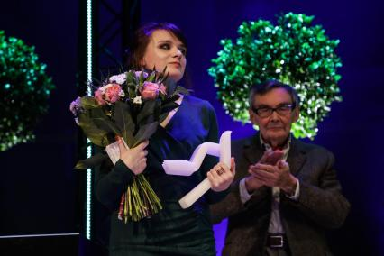 Natalia Bartczak jest laureatką Nagrody POLIN 2019. Na zdjęciu Natalia Bartczak z bukietem kwiatów i Nagrodą POLIN 2019. W tle przewodniczący Kapituły Nagrody POLIN 2019 Marian Turski.