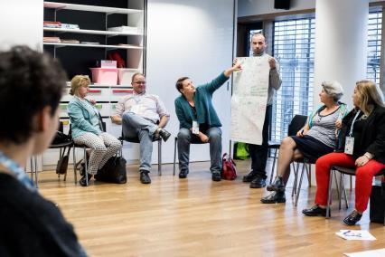 Szkolenie dla nauczycielek i nauczycieli o przeciwdziałaniu przemocy w szkole w Muzeum POLIN. Na zdjęciu w sali zajęć, w okręgu, siedzą na krzesłach mężczyźni i kobiety. Jeden z mężczyzn stoi, trzyma płachtę papieru z notatkami. Kobieta po jego lewej stronie wskazuje na te notatki, opowiada coś innym osobom.