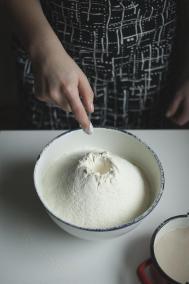 TISZ Festiwal: Finisaż. Na zdjęciu widać miskę przesianej mąki, która stoi na stole. W mące zrobione zagłębienie, na rozczyn drożdży - stoi on obok, przygotowany do wymieszania z mąką