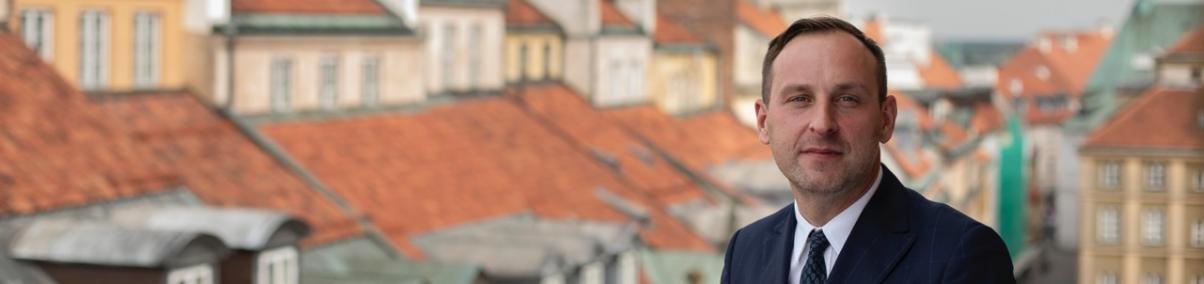 Dr Jarosław Trybuś, w tle widoczne dachy warszawskiego Starego Miasta, fot. Dawid Żuchowicz