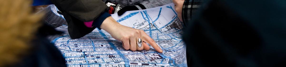 Wędrujący Uniwersytet Muranowski - spotkanie XIII. Na zdjęciu: widok mapy Muranowa, trzymanej przez kilka osób. Widać dłoń jednej z nich, wskazującej jakiś punkt na mapie.