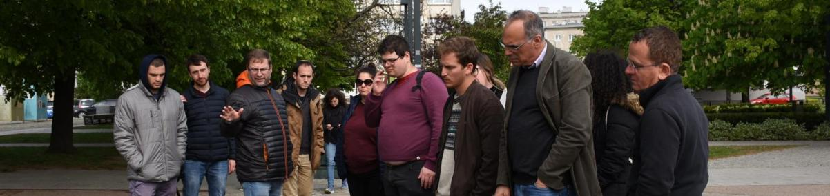 Wizyta studentów z Uniwersytetu Hebrajskiego z Izraela. Na zdjęciu: Grupa kobiet i mężczyzn, ubranych w wiosenne kurtki, stoi w wśród drzew przy pomniku. Jeden z mężczyzn gestykuluje, opowiada coś innym zgromadzonym.