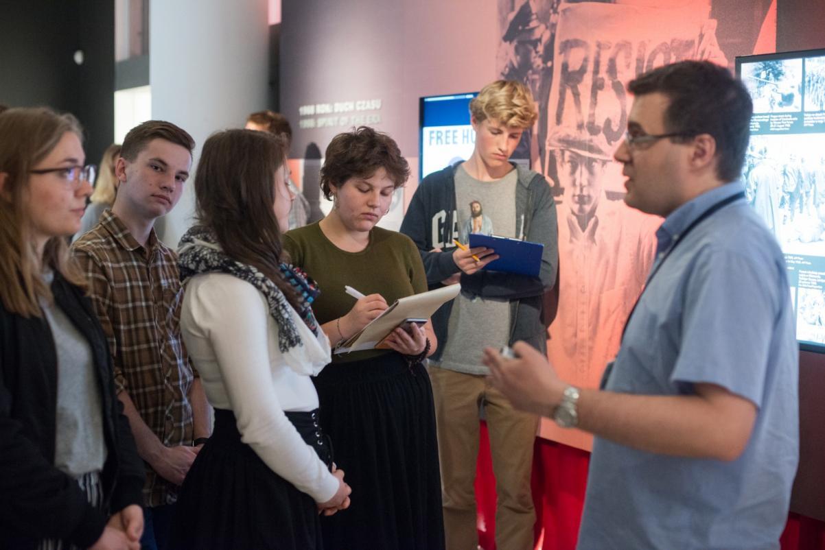 Przyjazna Polska. Młodzież przeciw mowie nienawiści - warsztaty dla szkół, Na zdjęciu: grupa młodzieży stoi po lewej stronie zdjęcia, na przeciwko nich stoi mężczyzna, który gestykuluje i tłumaczy coś