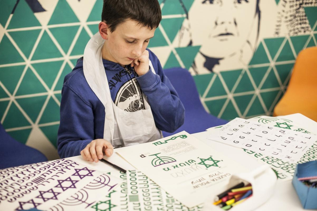 Warsztaty dla szkół w Muzeum POLIN. Na zdjęciu chłopiec pochylony nad kartką z treścią w języku hebrajskim. Zamyślony. Opiera głowę na ręce.