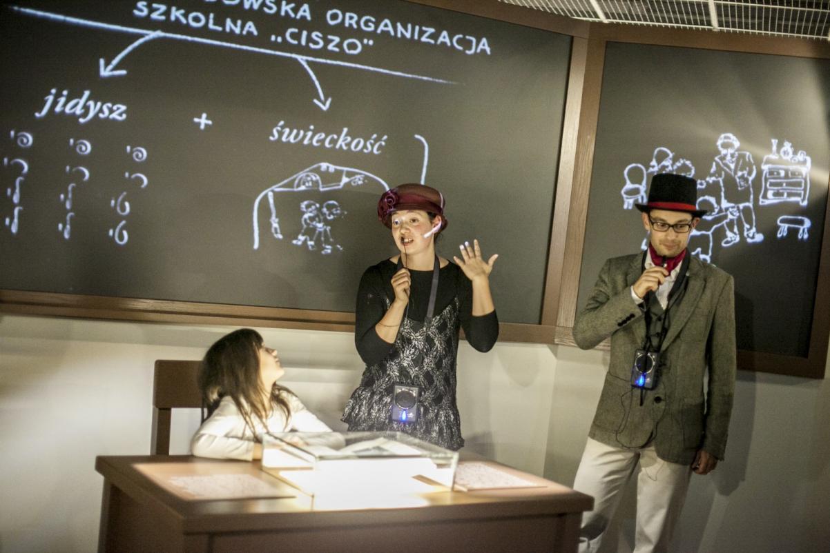 Warsztaty dla szkół - Muzeum POLIN. Przy tablicy szkolnej stoją kobieta i mężczyzna w przebraniach z dawnych czasów. Za biurkiem siedzi dziewczynka, która patrzy w ich stronę. Biurko oświetlone jest przez lampkę. Na tablicy wykresy i grafy.
