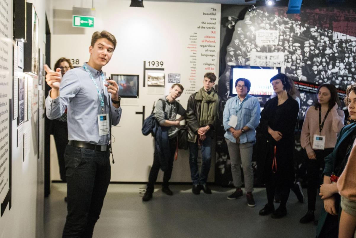 Grupa młodzieży znajduje się w przestrzeni wystawy, poświęconej okresowi II Wojny Światowej. Jeden z chłopców stoi po lewej stronie przed ekspozycją i prezentuje ją pozostałym, którzy stoją po prawej stronie - warsztaty dla klas 7-8 szkoły podstawowej w Muzeum POLIN