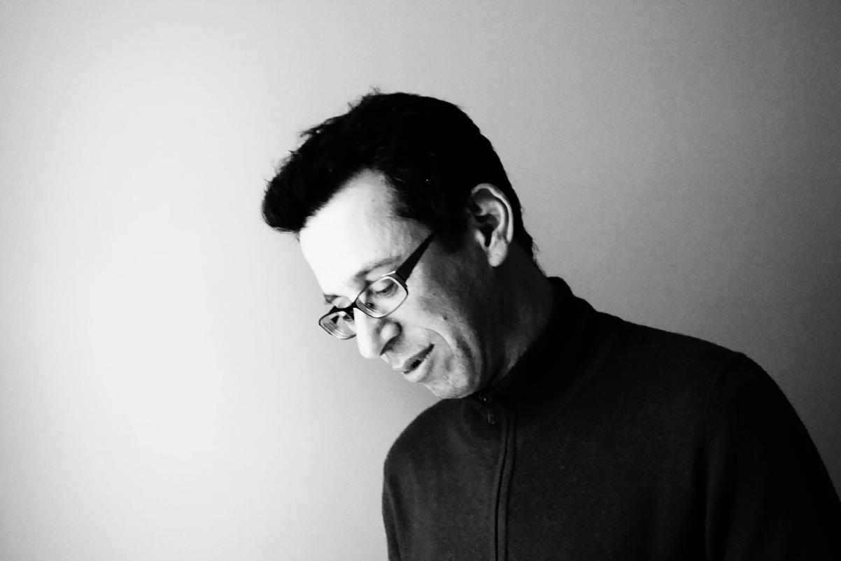 Spotkanie w Assafem Gavronem w ramach Czytelni POLIN. Na zdjęciu mężczyzna (Assaf Gavron), widoczny od piersi w górę. Stoi bokiem pochyla się do przodu z zamyśloną miną. Ma krótkie ciemne włosy i okulary. Zdjęcie czarno-białe.