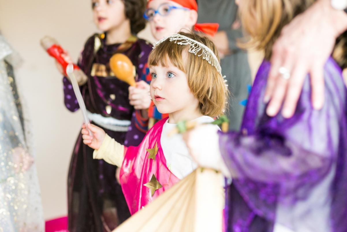 Warsztaty dla dzieci - Muzeum POLIN. Na zdjęciu, w otoczeniu innych osób w strojach karnawałowych, stoi dziewczynka w przebraniu. Ma w ręku różdżkę.