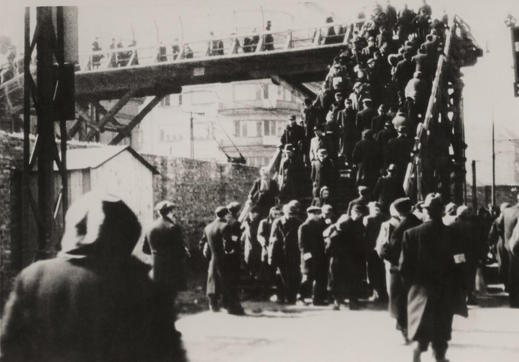 Warsztaty edukacyjne dla szkół ponadpodstawowych. Na zdjęciu archiwalnym z czasów istnienia getta warszawskiego widać grupy ludzi w czarnych ubraniach, którzy przechodzą kładką nad murem getta