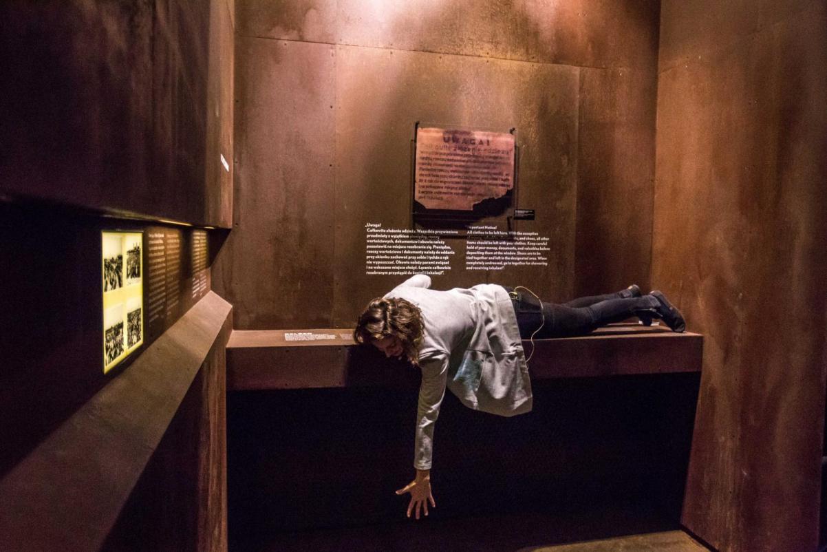 Choreograficzne oprowadzenie po wystawie stałem Muzeum POLIN. Na zdjęciu: Kobieta leży na półce na wystawie stałej w przestrzeni poświęconej Zagładzie Żydów. Ręką próbuje dotknąć podłogi. Twarz ma zasłonięta włosami.