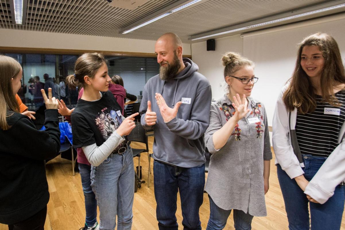 Grupa ludzi - młodych i starszych - stoi w kręgu. W centrum kadru młoda dziewczyna i mężczyzna z brodą porozumiewają się za pomocą języka migowego - warsztaty dla klas 7-8 szkoły podstawowej w Muzeum POLIN