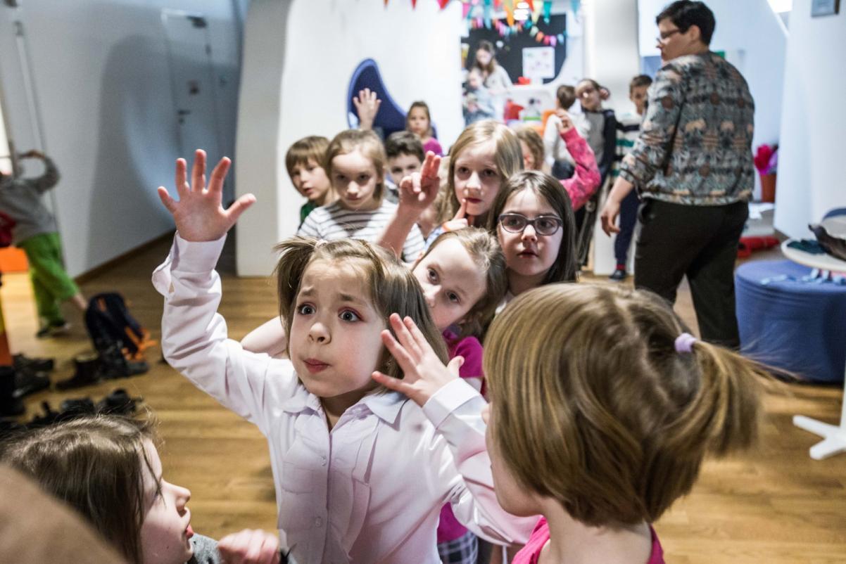 Dzieci i ryby głosu nie mają? O prawach dziecka i Januszu Korczaku - w sali z białymi ścianami stoi grupa dzieci. Na pierwszym planie dziewczynka w białej bluzce, która żywiołowo gestykuluje i coś tłumaczy.