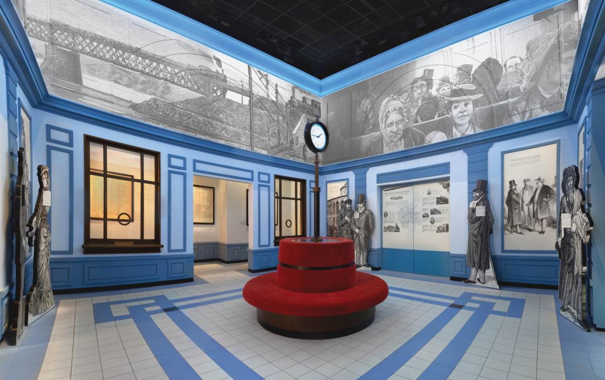 Warsztaty edukacyjne dla szkół ponadpodstawowych. Na zdjęciu: sala dworca, zrekonstruowana w przestrzeni muzeum. Na środku pomieszczenia czerwone okrągłe siedzisko, w którym na środku tkwi na rurze wielki zegar dworcowy